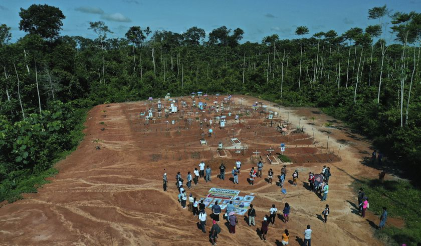 Relatives of people who died from COVID-19 gather next to a clandestine mass grave on the outskirts of Iquitos, Peru, Saturday, March 20, 2021. Local authorities approved the mass burials but never told the families, who believed their loved ones were interred in the nearby local cemetery — and only months later discovered the truth.(AP Photo/Rodrigo Abd)