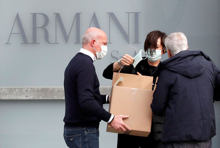 A worker holds a face mask outside the theatre where the Italian designer Giorgio Armani said his Milan Fashion Week show would take place in Milan