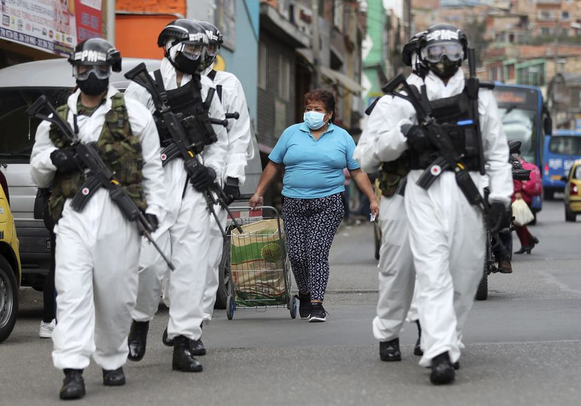 Soldiers in protective gear amid the COVID-19 pandemic patrol in Ciudad Bolivar, an area with high cases of the new coronavirus in Bogota, Colombia, Monday, July 13, 2020. The mayor of Bogota ordered tight restrictions in areas seeing the highest contagion. (AP Photo/Fernando Vergara)