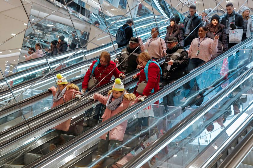 FILE PHOTO: People ride an escalator in H & M during a Black Friday sales event in Manhattan, New York City