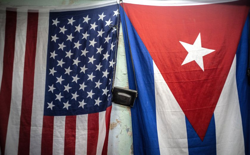 """A U.S. and Cuban flags hang from a wall with an old photo camera hung in between in Havana, Cuba, Monday, Jan 11, 2021. The Trump administration has re-designated Cuba as a """"state sponsor of terrorism"""" in a move that hits the country with new sanctions shortly before President-elect Joe Biden takes office. (AP Photo/Ramon Espinosa)"""