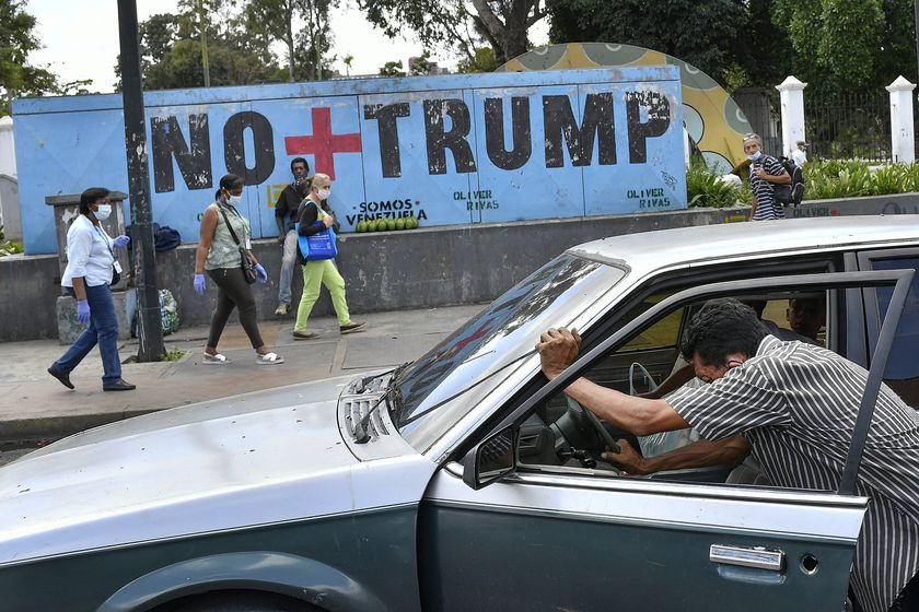 """A man pushes his car that ran out of gas as people wearing protective face masks as a precaution against the spread of the new coronavirus, walk past a mural with a message that reads in Spanish: """" No more Trump"""" in Caracas, Venezuela, Sunday, Nov. 8, 2020. Venezuelan President Nicolas Maduro has sent a congratulatory message to U.S. President-elect Joe Biden who won the U.S. presidential election, defeating incumbent Donald Trump. (AP Photo/Matias Delacroix)"""