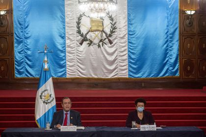 Guatemalan President Alejandro Giammattei, left, accompanied by Health minister Amelia Flores, speaks during a press conference at the National Palace in Guatemala City, Tuesday, July 27, 2021. The U.S. government has suspended cooperation with Guatemala's Attorney General's Office in response to the firing of its top anti-corruption prosecutor Juan Francisco Sandoval according to U.S. State Department. (AP Photo/Oliver de Ros)