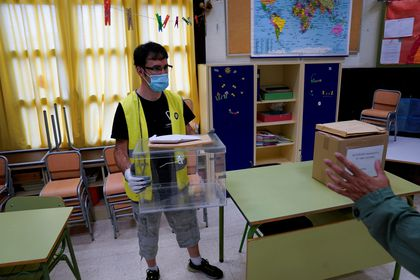 A worker wearing a protective face mask arranges an urn at a polling station ahead of Basque regional elections on Sunday, amid the coronavirus disease (COVID-19) outbreak, in Bilbao
