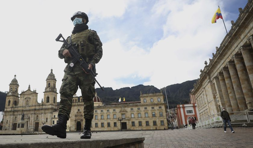 A soldier wearing a protective face mask walks in Bolivar Square in Bogota, Colombia, Tuesday, July 21, 2020, amid the new coronavirus pandemic. (AP Photo/Fernando Vergara)