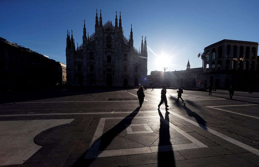 People walk through Duomo square, as a coronavirus outbreak continues to grow in northern Italy, in Milan