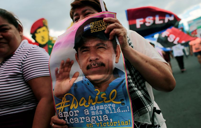 """A woman supporter holds a pictures on Nicaraguan President Daniel Ortega during a march called""""Brave Women! Victorious women!"""" to mark International Women's Day in Managua"""
