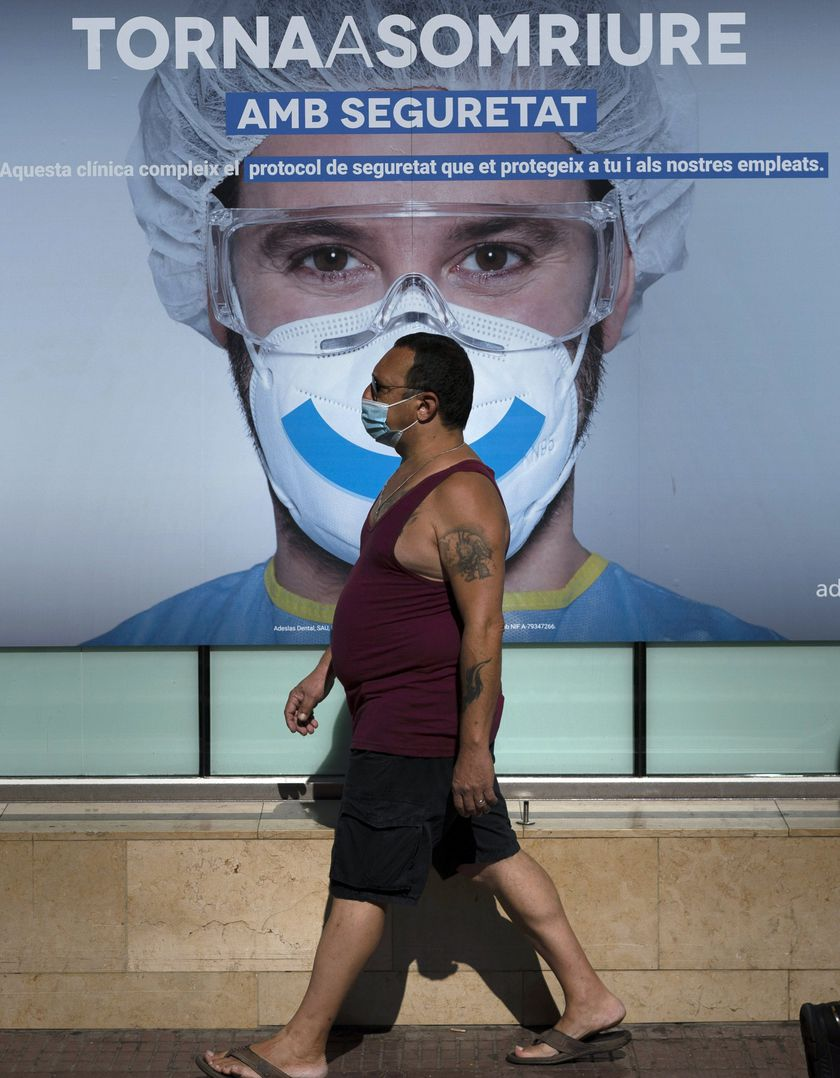 A man wearing face mask walks past an advertising of a private clinic in Barcelona, Spain on Monday Aug. 31, 2020. Spain, with nearly 440,000 infections of the new virus since February, has become western Europe's hardest hit country by a new surging wave of fresh outbreaks. (AP Photo/Emilio Morenatti)