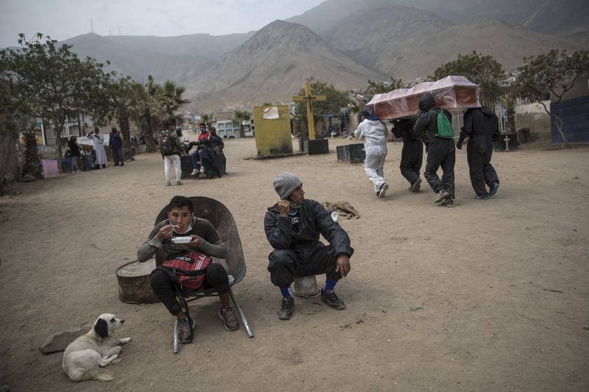 "A cemetery worker sits in his wheelbarrow during his lunch breaj as fellow workers walk past shouldering a casket that contains the remains of a person who is suspected to have died from symptoms related to the new coronavirus, at the ""Martires 19 de Julio"" cemetery, in Comas, on the outskirts of Lima, Peru, Saturday, July 4, 2020. Along with cremations, burials have continued, with nearly 200 deaths daily due to a rate of infection that continues to be among the world's highest. Many families must hunt down spots in economical and far-flung cemeteries on the outskirts of Lima. (AP Photo/Rodrigo Abd)"