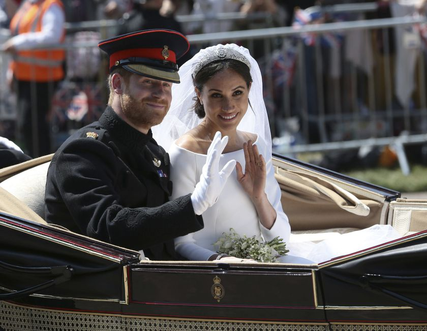 FILE - In this Saturday, May 19, 2018 file photo, Britain's Prince Harry and Meghan Markle ride in an open-topped carriage after their wedding ceremony at St. George's Chapel in Windsor Castle in Windsor, England. Prince Harry and his wife Meghan are ending their lives as senior members of Britain's royal family and starting an uncertain new chapter as international celebrities and charity patrons. In January the couple shocked Britain by announcing that they would step down from official duties, give up public funding, seek financial independence and swap the U.K. for North America. The split becomes official on March 31. (Aaron Chown/pool photo via AP, file)