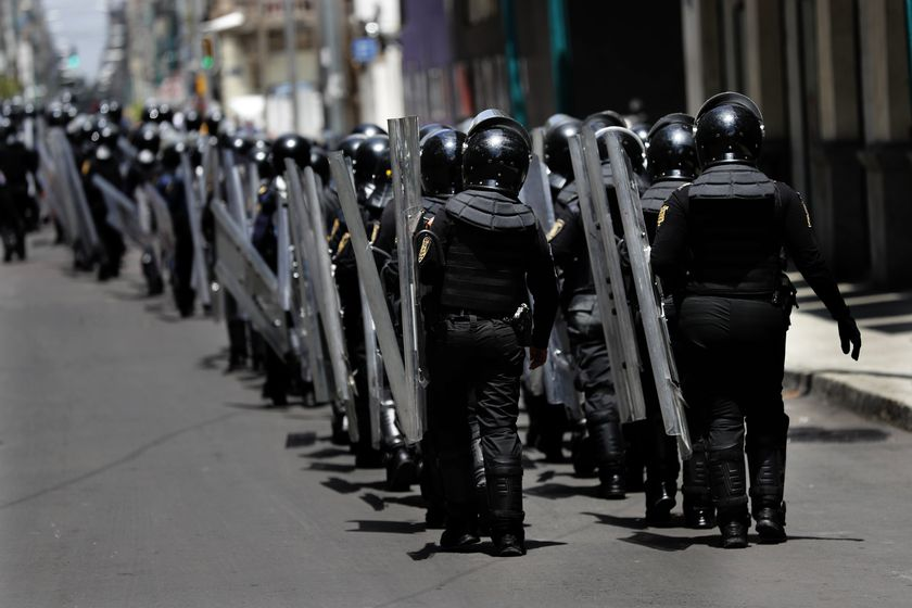 Police in riot gear assemble at a distance, as a handful of protesters stopped traffic in Paseo de la Reforma, one of central Mexico City's main thoroughfares, Saturday, July 18, 2020. The few protesters carried signs condemning the president's Maya Train project, and calling for the release of people detained during previous violent anarchist protests. (AP Photo/Marco Ugarte)