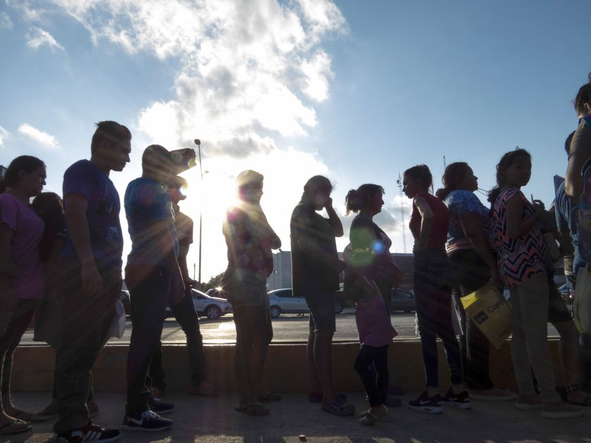 FILE - Migrants seeking asylum wait in line with their case paperwork during a weekly trip by volunteers, lawyers, paralegals and interpreters to the migrant campsite outside El Puente Nuevo in Matamoros, Mexico, Saturday, Oct. 5, 2019. A federal judge on Monday, Aug. 31, 2020, blocked U.S. Customs and Border Protection employees from conducting the initial screening for people seeking asylum, dealing a setback to one of the Trump administration's efforts to rein in asylum. (Denise Cathey/The Brownsville Herald via AP, File)