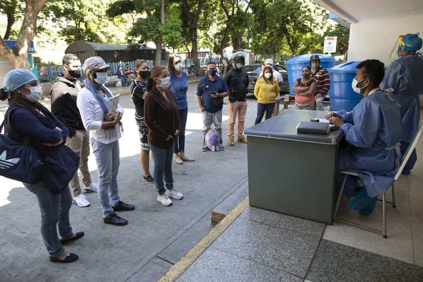 """Dr. Wilfredo Sifontes, right, speaks to families who have family hospitalized in the COVID-19 wing, outside José Gregorio Hernández Hospital in the Catia neighborhood of Caracas, Venezuela, Friday, Sept 4, 2020. Sifontes, who oversees the hospital's emergency services including its coronavirus wing, described having a fever, cough and feeling sick. Though he oversees testing kits, he himself was never tested and continued to clock in. He dismissed the threat of the coronavirus, comparing it to a """"common flu"""" that's sparked needless panic.   (AP Photo/Ariana Cubillos)"""