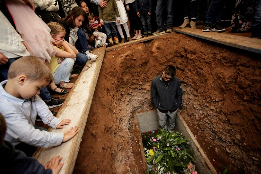 FILE PHOTO: A relative reacts during the burial of Miller and her children who were killed by unknown assailants in LeBaron