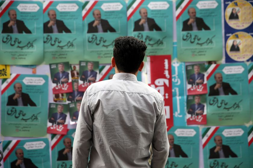 A man looks on parliamentary election campaign posters in Tehran