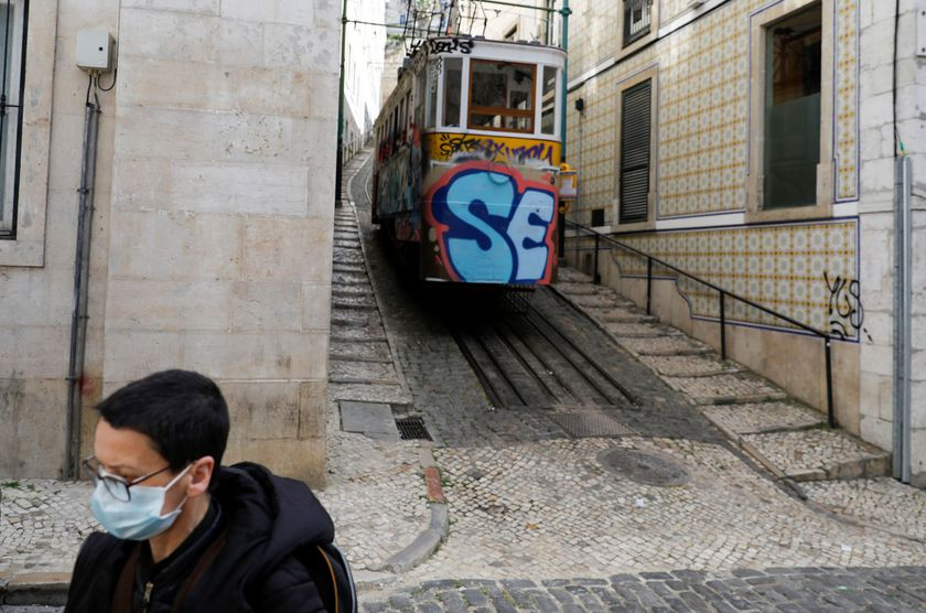 A woman is pictured wearing a mask as she walks next to a tram in downtown Lisbon