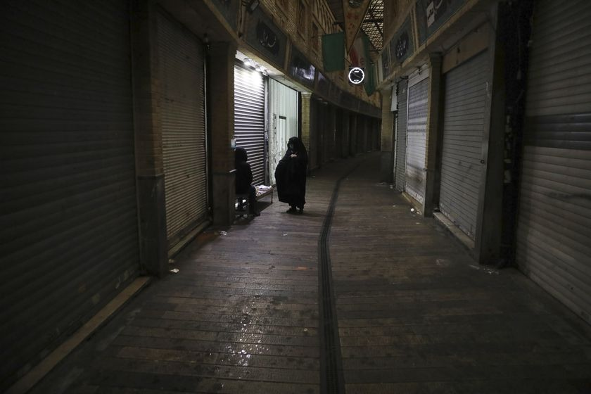 A woman talks with a vendor in a closed bazaar in northern Tehran, Iran, Nov. 22, 2020. Iran on Saturday shuttered businesses and curtailed travel between its major cities, including the capital of Tehran, as it grapples with the worst outbreak of the coronavirus in the Mideast region. (AP Photo/Vahid Salemi)