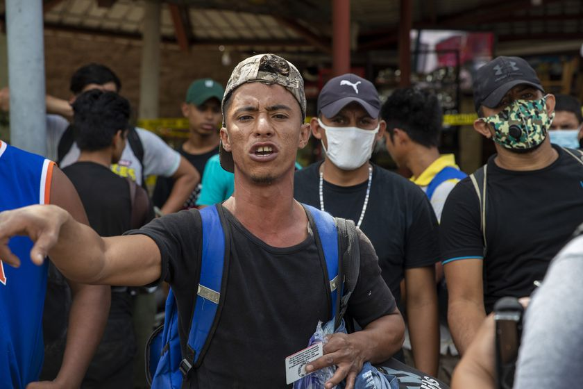 A Honduras migrant gestures as he talks with police before returning home, in Morales, Guatemala, Saturday, Oct. 3, 2020. Early Saturday, hundreds of migrants who had entered Guatemala this week without registering were being bused back to their country's border by authorities after running into a large roadblock. (AP Photo/Moises Castillo)