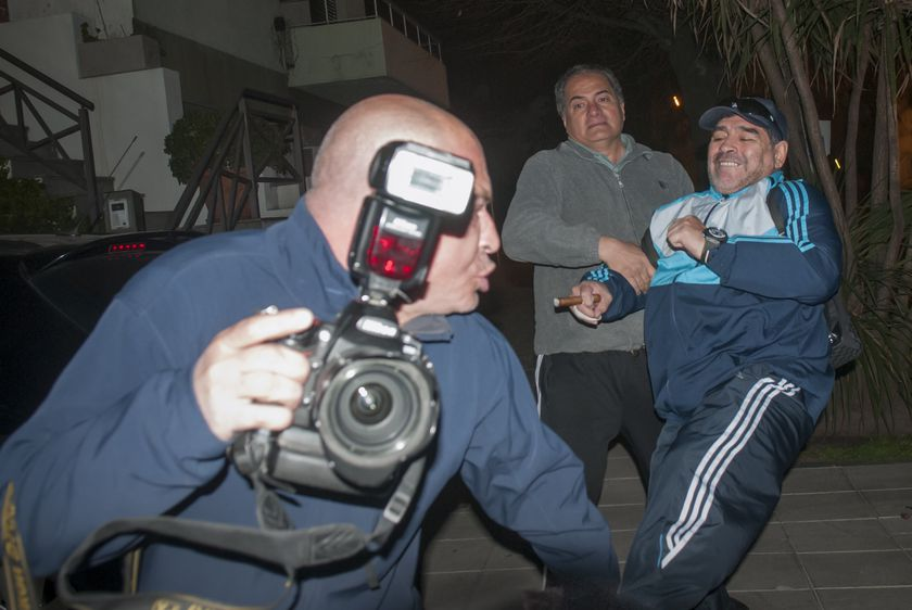 Argentina's Diego Maradona, right, reaches with his leg to try to kick photographer Enrique Garcia Medina, front, outside the home of Maradona's father in Buenos Aires, Argentina, Sunday, July 28, 2013. The man holding Maradona back is unidentified.  Garcia Medina filed a police complaint alleging that the former soccer star and coach attacked him. (AP Photo/Caras Magazine) NO PUBLICAR EN ARGENTINA - NO PUBLICAR EN INTERNET - ARGENTINA OUT - ONLINE OUT