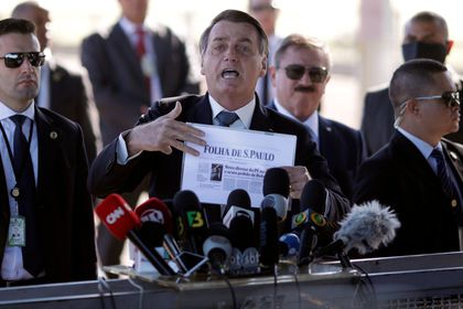 FILE PHOTO: Brazil's President Bolsonaro holds a paper with a print of the first page of newspaper Folha de Sao Paulo, in Brasilia