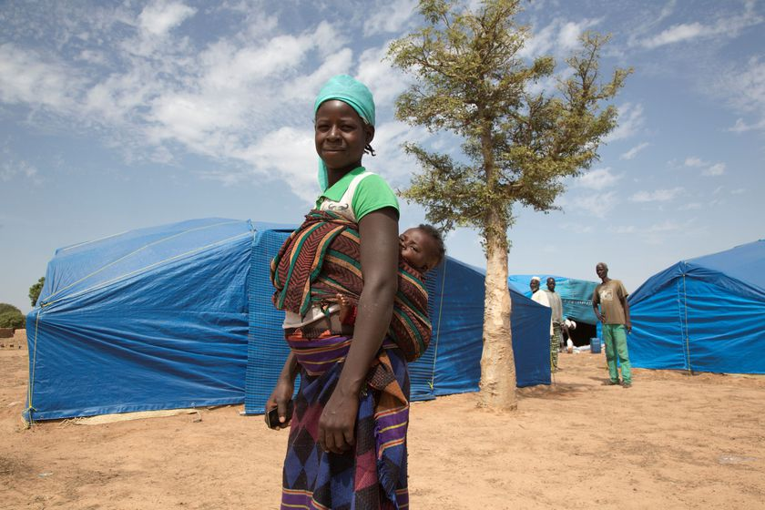 A woman carries her child as she stands at an IDP camp in Pissila