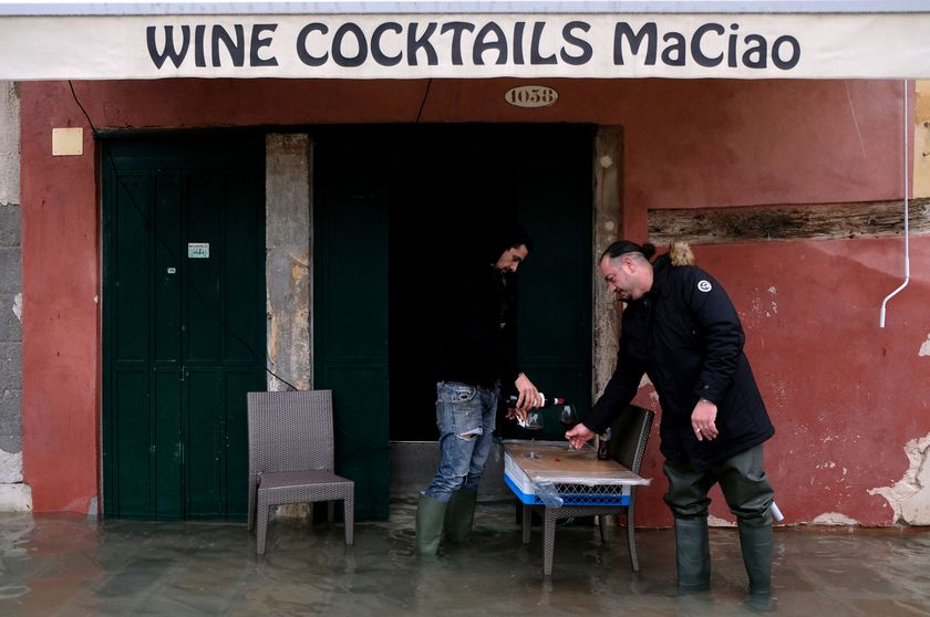 Two men pour a glass of wine outside their flooded bar during exceptionally high water levels in Venice